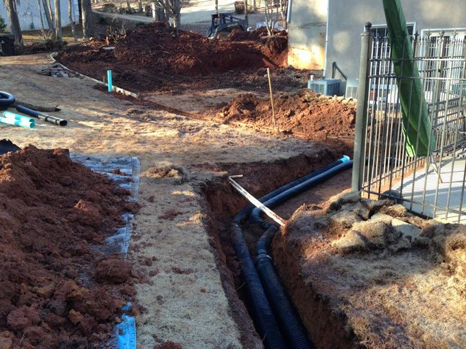 "peachtree city landscaper installs an underground drain systems using 6"" pipe"